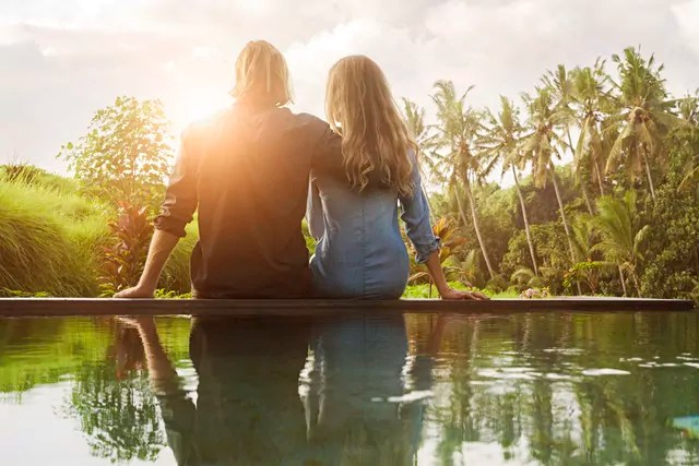 Embracing couple sitting on the edge of a pool and enjoying stunning view of sunset in lush tropical garden
