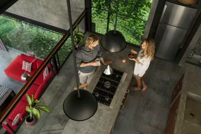 Top view of couple standing in modern design kitchen with glass facade surrounded by lush garden
