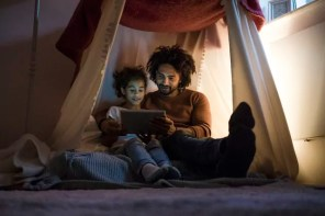 Father and daughter sitting in dark children's room, looking at digital tablet