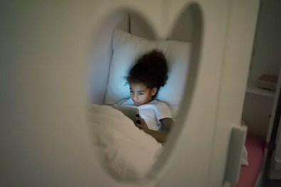 Little girl sitting in dark children's room, looking at digital tablet