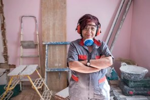 Portrait of senior woman with ear protection and respirator at construction site