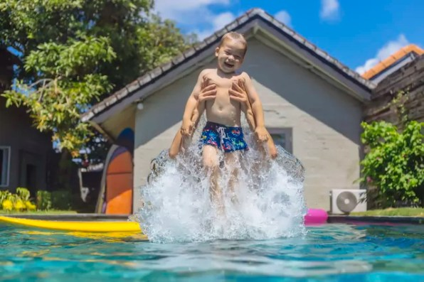 Father and son having fun in swimming pool