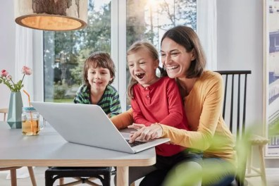 Happy mother with two children using laptop at home