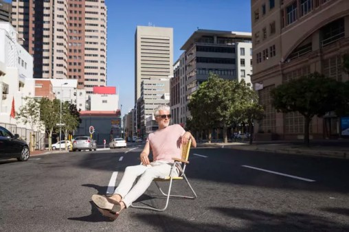 Mature man sitting on chair in the street, wearing sunglasses