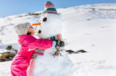 Girl playing with snowmen in winter