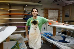 Portrait of smiling man standing by surfboards in workshop