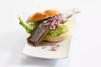 Sandwich stuffed with salted herring in plate