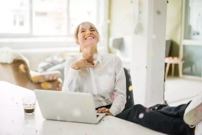 Confetti falling on businesswoman with laptop in office