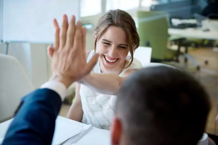Happy businesswoman and businessman high fiving