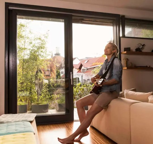 Mature woman singing and playing guitar in the living room