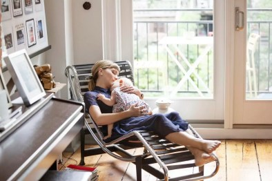 Mother and baby girl sleeping on lounge chair at home