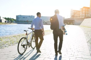 Two businessmen walking with bicycle and skateboard at the riverbank