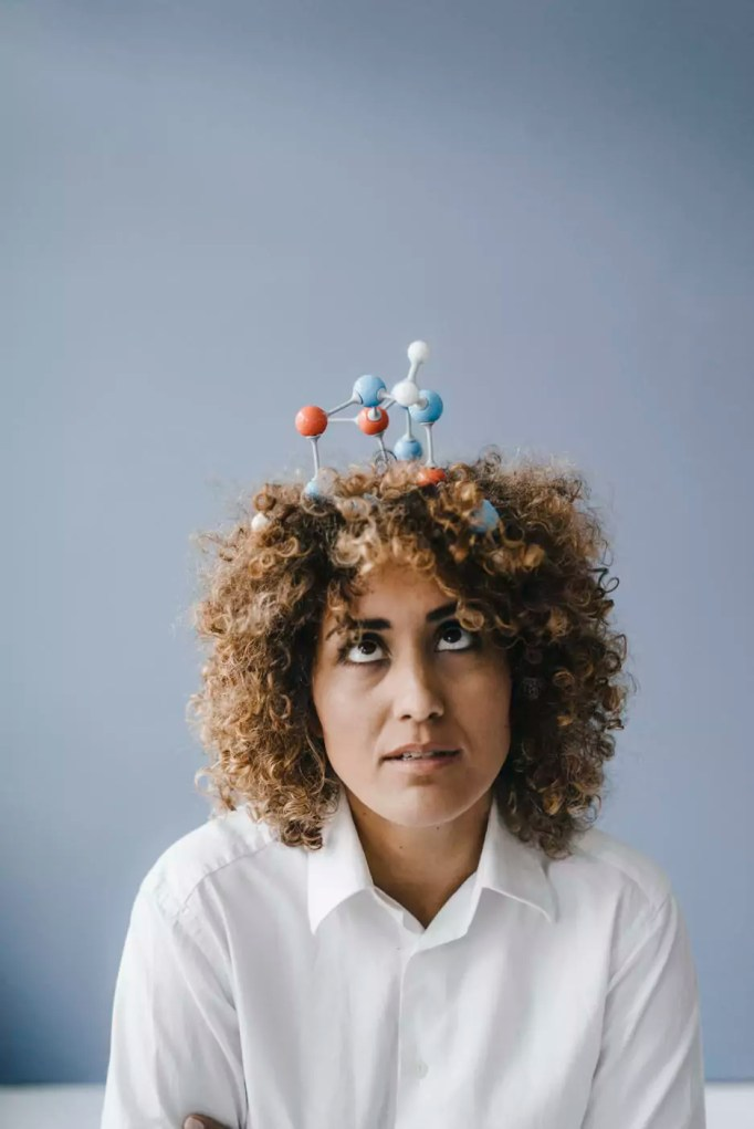 Young woman with molecule model in her hair