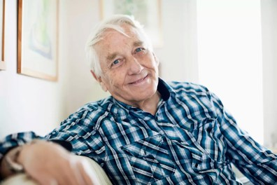 Portrait of smiling elderly man sitting in living room