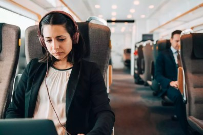 Mid adult businesswoman using headphones and laptop while traveling in train