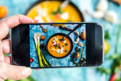 Woman photographing with a smartphone a sweet potato soup