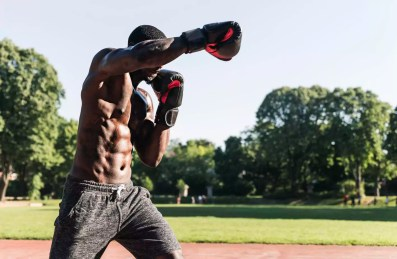 Young Afro-American man training boxing on sports field, outdoors