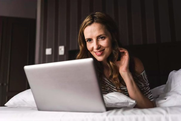 Smiling woman lying on bed at home looking at laptop