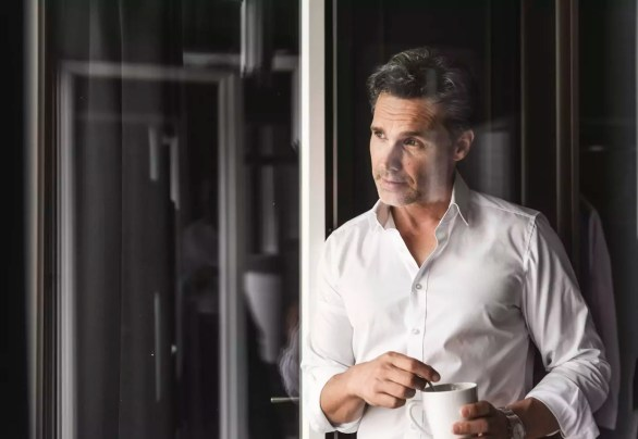 Businessman with cup of coffee looking out of window at home