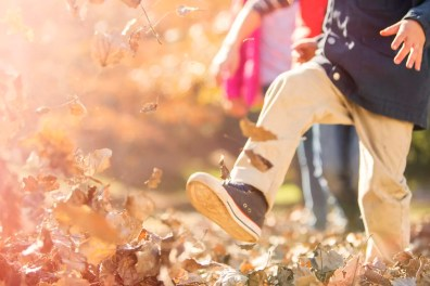 Boy running and jumping in autumn leaves
