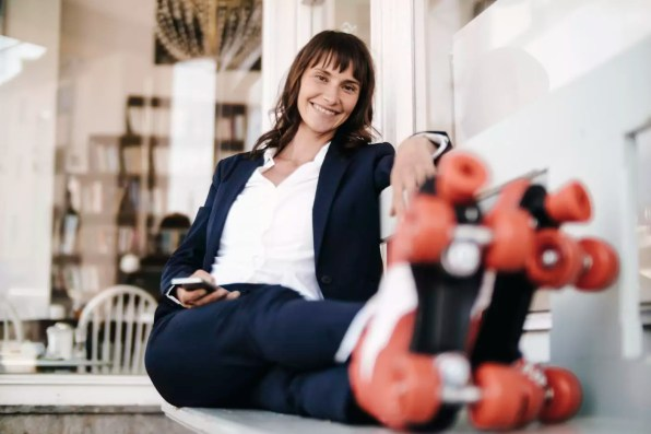 Businesswoman wearing roller skates, holding smartphone