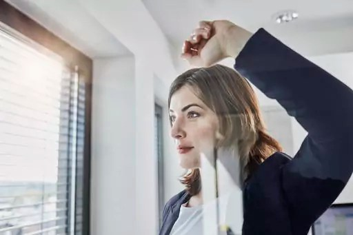 Confident young businesswoman looking out of window in office