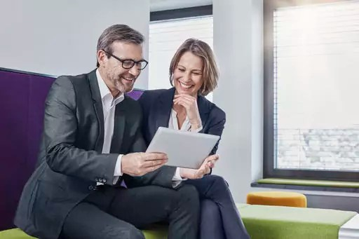Smiling businessman and businesswoman using tablet in office lounge together