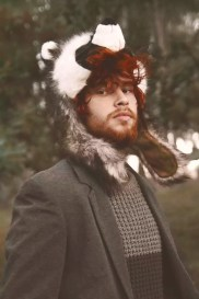 Portrait of redheaded young man wearing raccoon hat in the woods