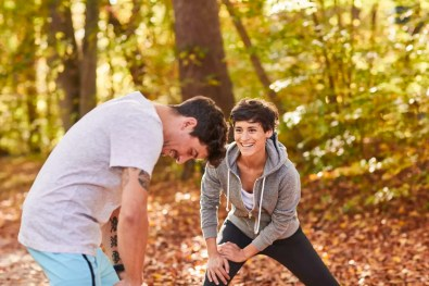Couple stretching in autumn forest