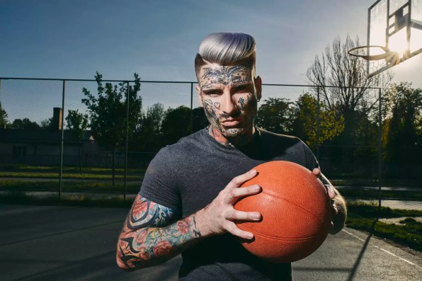 Portrait of tattooed young man with basketball on court