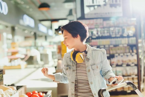 Young woman with headphones browsing, grocery shopping in market