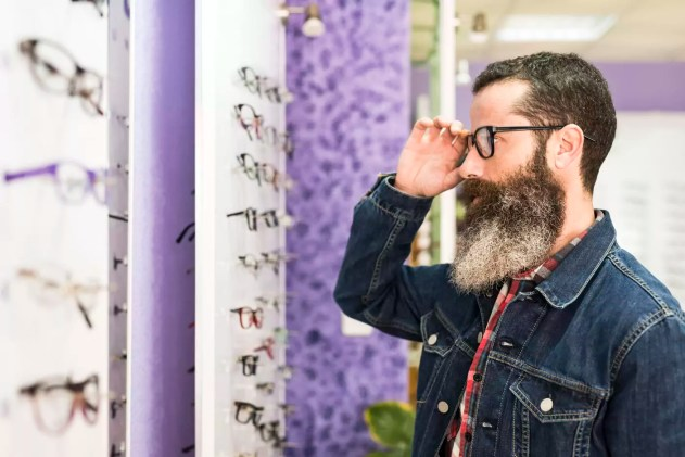 Bearded man in optical store trying on glasses and looking in mirror