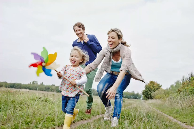 Family on a trip with daughter holding pinwheel