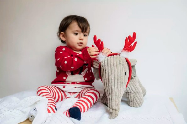 Baby girl playing with reindeer antlers headband and toy elephant