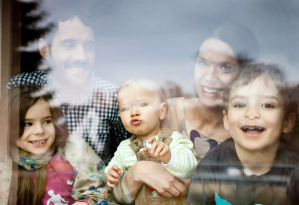 Happy family of five looking through window pane