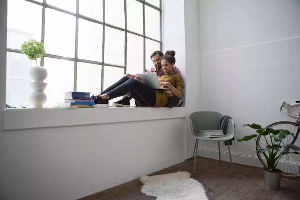 Young couple sitting on window sill using laptop