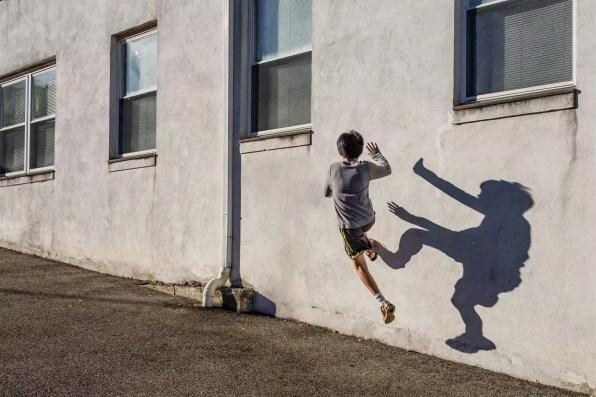 Rear view of teenage boy jumping over wall during sunny day