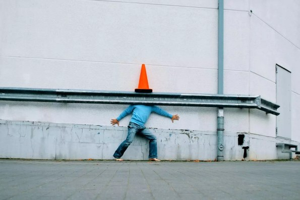 A man hiding underneath a traffic cone against a white wall