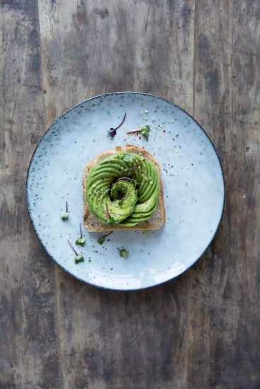 Open sandwich with sliced avocado in plate on wooden table