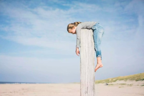 Little girl on the beach hanging on a pole