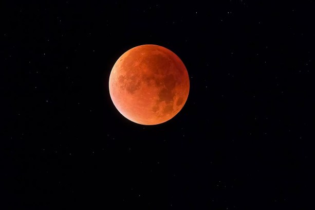 Total lunar eclipse with stars in background, blood moon