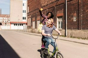 Young couple riding bicycle in the street, woman standing on rack, taking selfies