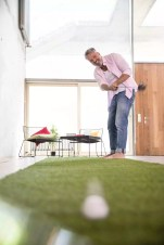 Happy casual businessman playing golf on artificial turf in a loft