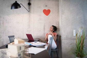 Businesswoman sitting at table in a loft under a heart on concrete wall