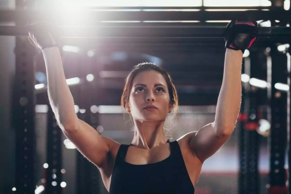 Close-up of young woman doing chin-ups at gym