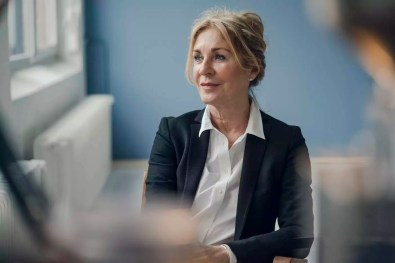 Senior businesswoman sitting on chair looking sideways