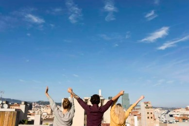 Spain Barcelona, three friends back portrait on a sunny day at a rooftop city view, urban friends group three young atractive happiness barcelona back