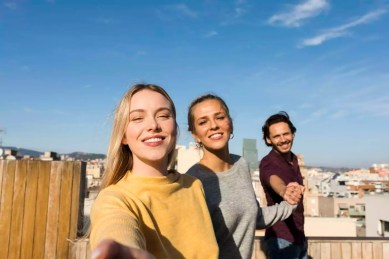 Spain Barcelona, three friends on a rooftop urban city view holding hands and trying to reach the camera, friendship three-person holding-hands young mixed-race rooftop sunny urban city barcelona
