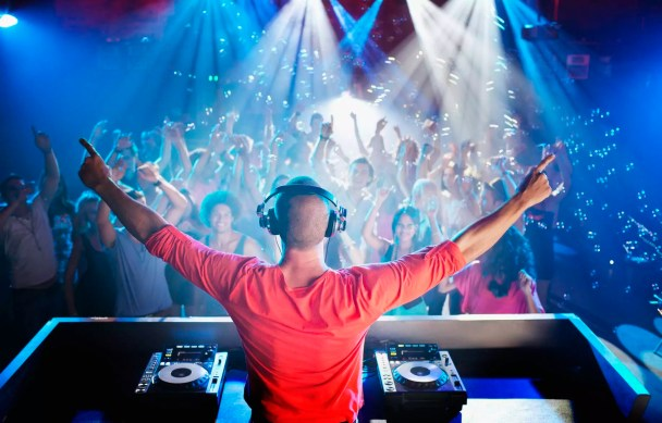 DJ with arms outstretched overlooking dance floor