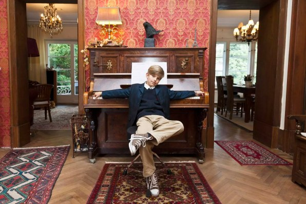 A boy with a cool attitude posing at an old-fashioned upright piano